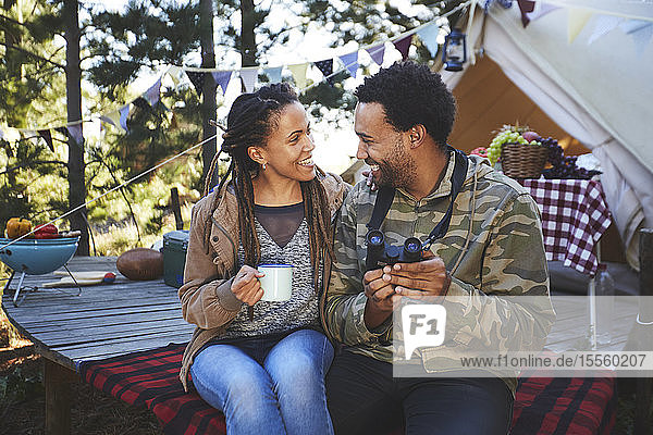 Affectionate young couple with binoculars drinking coffee at campsite
