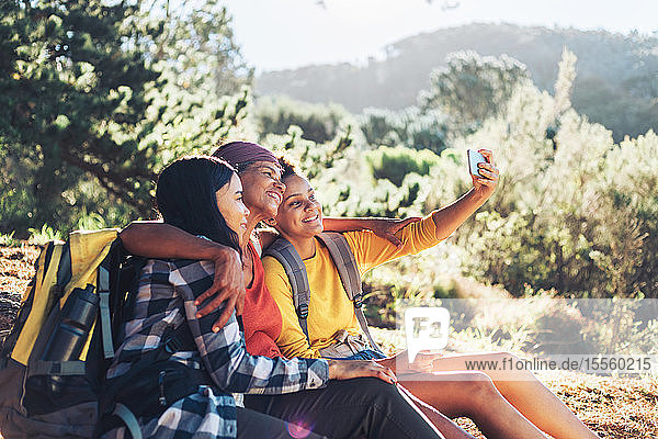 Happy mother and daughters taking selfie  hiking in sunny woods