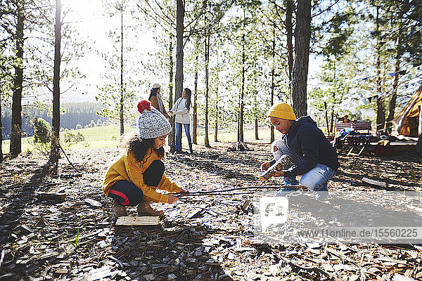 Brother and sister gathering kindling in sunny woods outside campsite