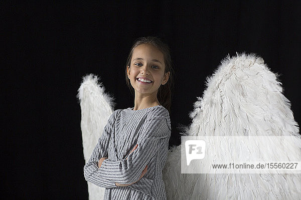 Portrait smiling  confident girl wearing angel wings Portrait smiling, confident girl wearing angel wings