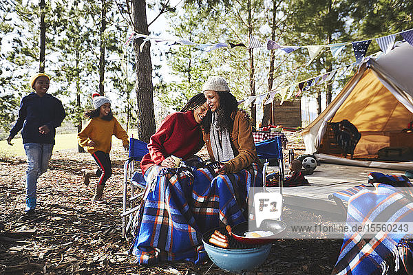 Happy  affectionate lesbian couple with kids relaxing at campsite in woods