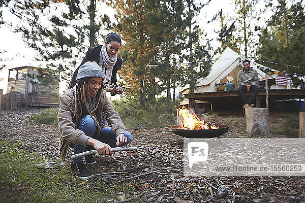 Friends gathering firewood kindling at campsite in woods