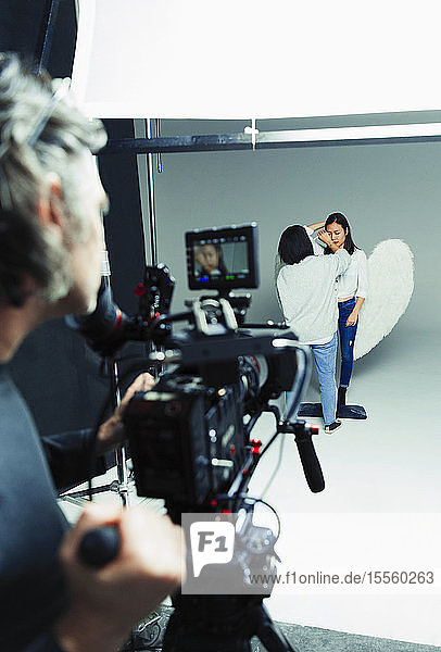 Photographer waiting for makeup artist and model in angel wings during studio photo shoot