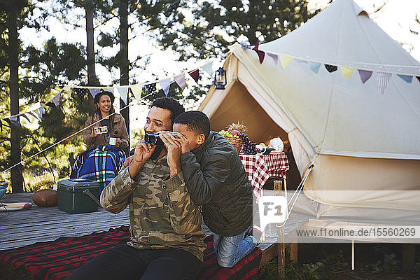 Curious father and son using binoculars outside yurt at campsite