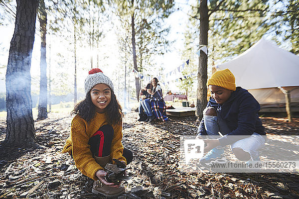 Portrait smiling girl gathering kindling at sunny campsite in woods