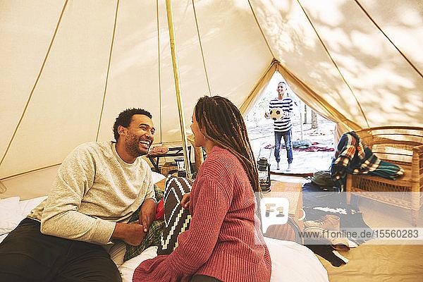 Happy couple relaxing in campsite yurt
