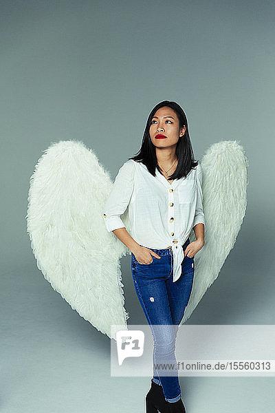 Portrait serene  thoughtful woman wearing angel wings Portrait serene, thoughtful woman wearing angel wings