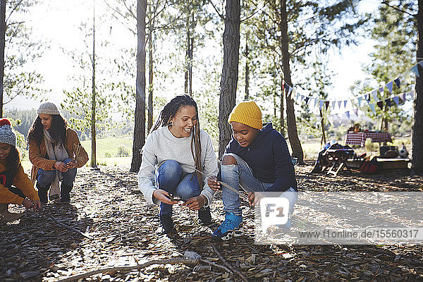 Mother and son gathering firewood kindling at campsite in sunny woods