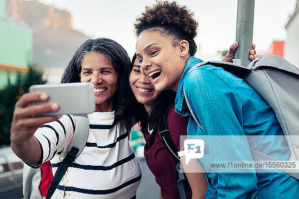 Happy mother and daughters backpacking  taking selfie with camera phone