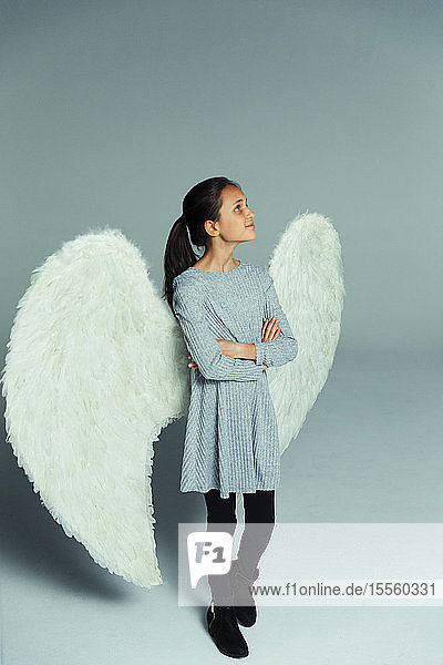 Portrait confident  curious girl wearing angel wings  looking up