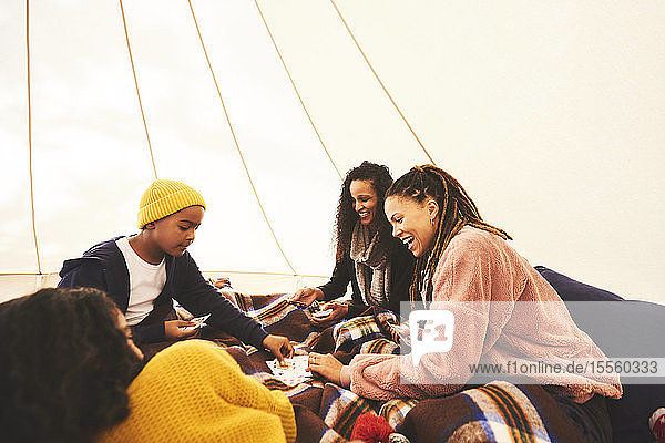 Happy lesbian couple and kids playing cards in camping yurt