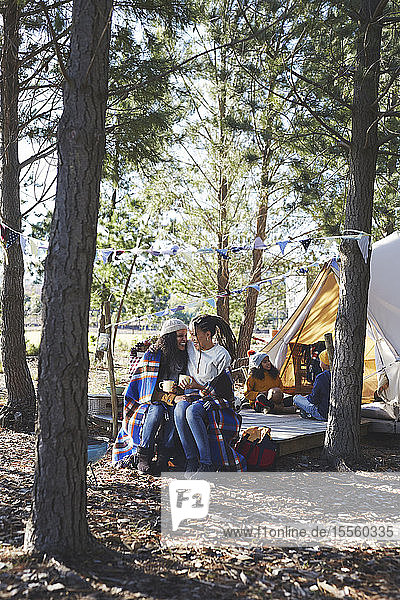 Happy  affectionate lesbian couple with kids relaxing  drinking coffee at campsite in woods
