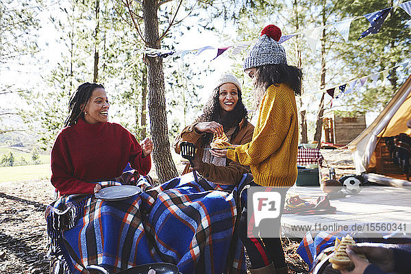 Happy lesbian couple and daughter enjoying breakfast at sunny campsite in woods