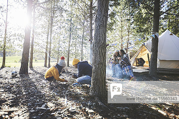 Lesbian couple watching kids gathering kindling at sunny campsite in woods