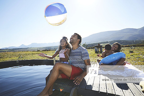 Playful family with beach ball at sunny  summer swimming pool