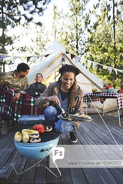 Smiling woman cooking vegetables on campsite grill
