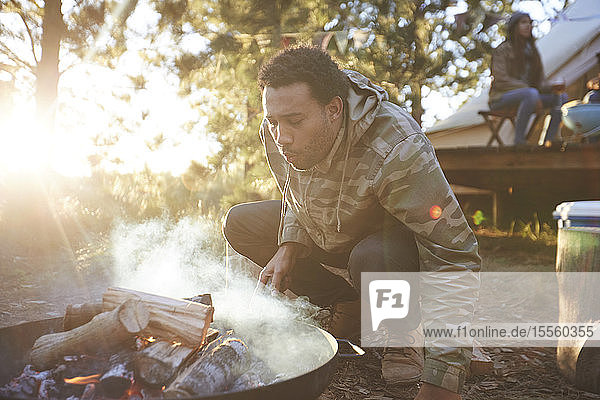Man blowing on campfire in sunny woods