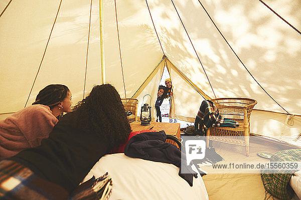 Curious kids peeking inside camping yurt