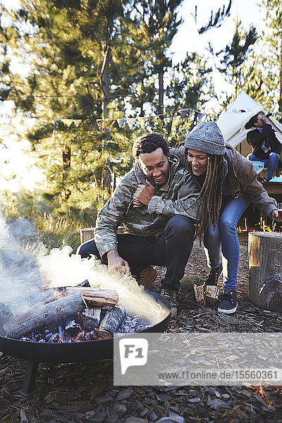 Happy couple tending to campfire at campsite in woods