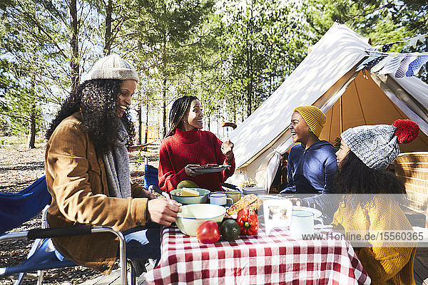 Lesbian couple and kids eating at sunny campsite