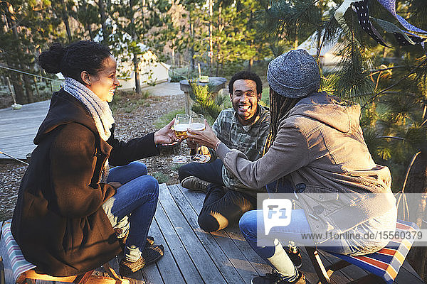 Happy friends drinking wine at campsite in woods