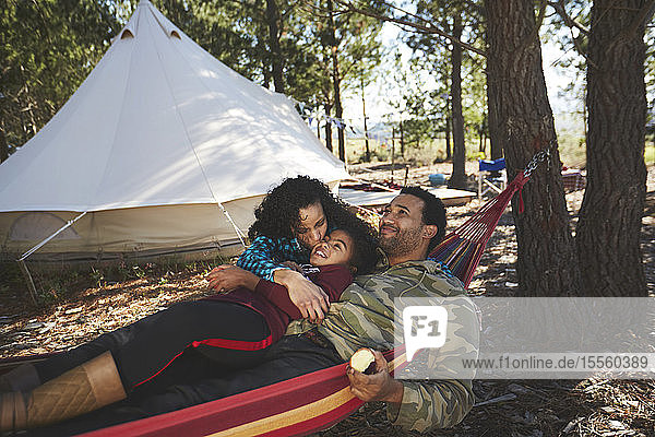 Happy  carefree family relaxing in hammock at campsite in woods