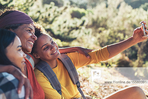 Happy mother and daughter hikers taking selfie with camera phone