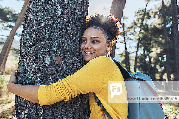 Happy  carefree young female hiker hugging tree in sunny woods