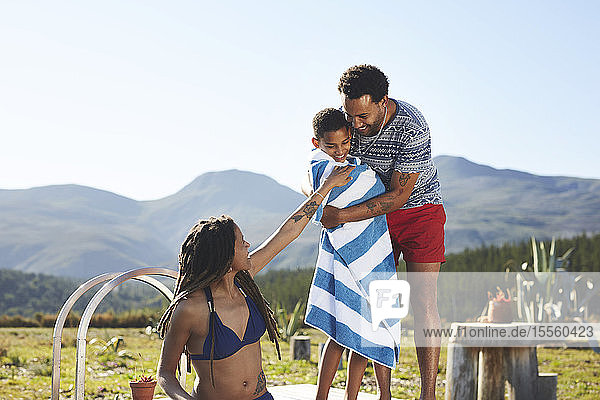 Happy,  affectionate family at remote,  sunny,  summer poolside