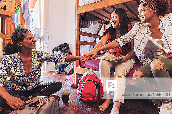 Mother and daughter backpackers joining hands  staying at youth hostel