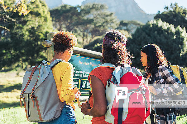 Female hikers looking at sign in sunny woods