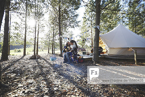 Happy  affectionate lesbian couple relaxing  drinking coffee at sunny campsite in woods
