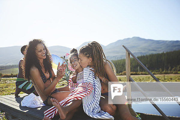 Affectionate lesbian couple and daughter at remote  sunny  summer poolside