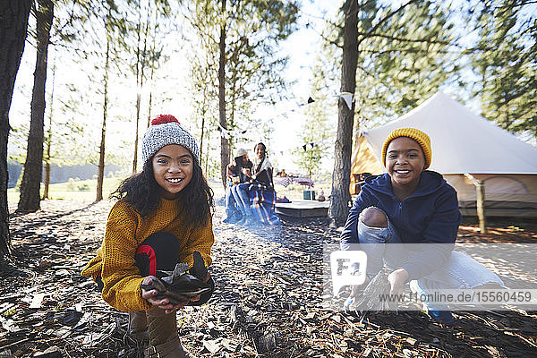 Portrait happy brother and sister playing in autumn leaves at sunny campsite in woods