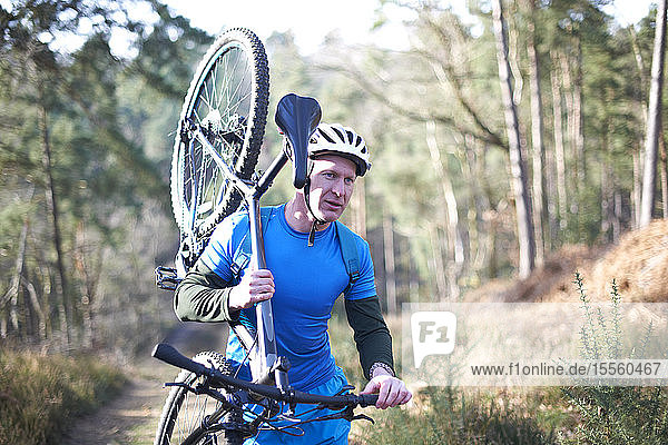 Male cyclist carrying bicycle on sunny trail in woods