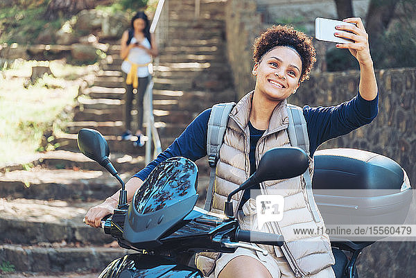 Young woman taking selfie with camera phone on motor scooter