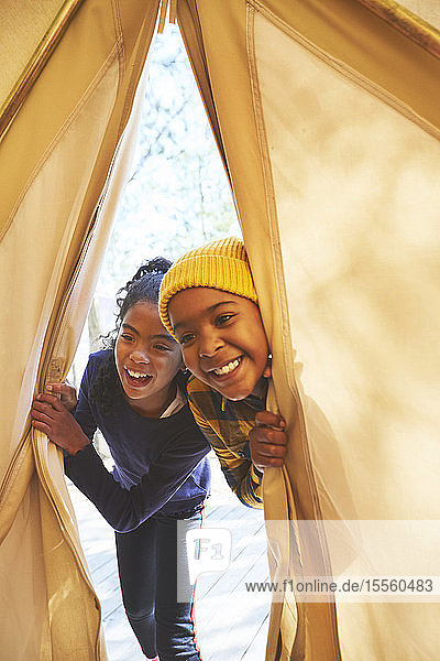 Playful brother and sister peeking into camping teepee