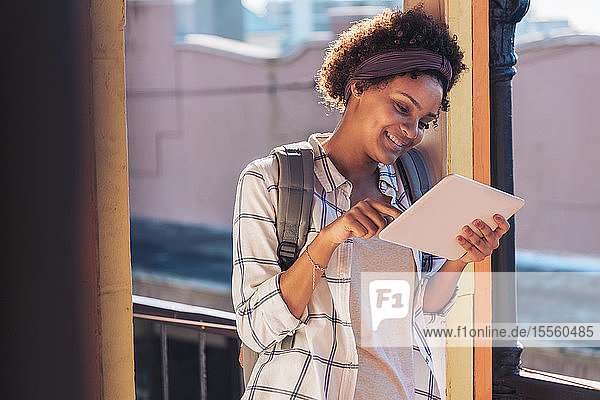 Young woman using digital tablet on sunny balcony