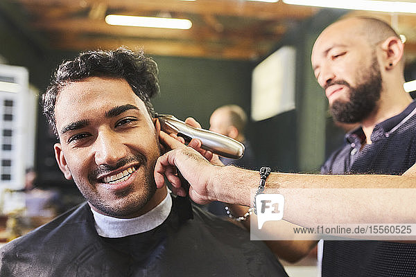 Portrait smiling young man receiving haircut at barbershop
