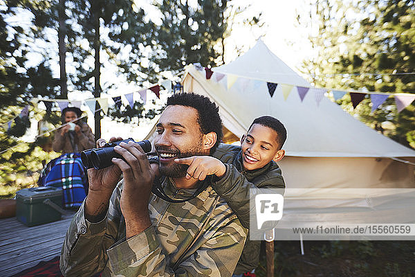 Happy  curious father and son with binoculars at campsite