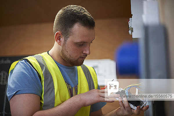 Male electrician student examining light switch in workshop