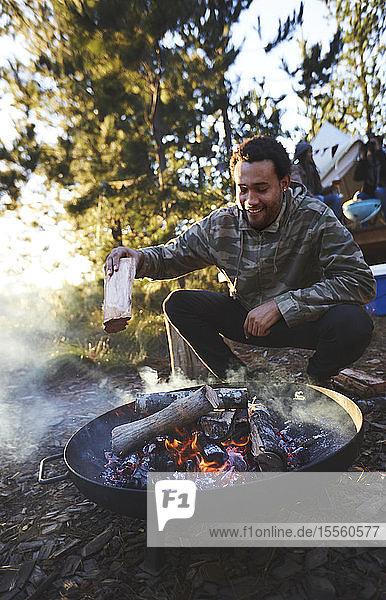 Man adding firewood to campsite campfire
