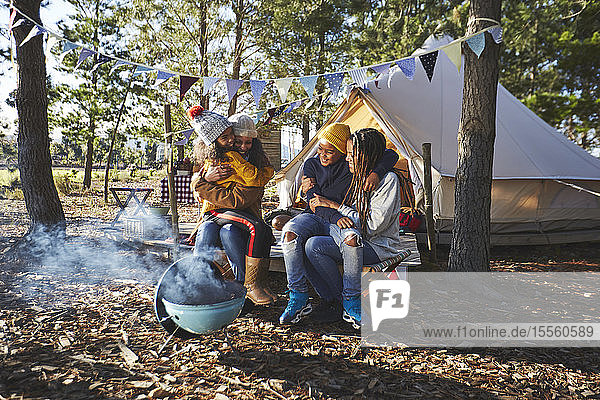 Happy  affectionate lesbian couple with kids at sunny campsite