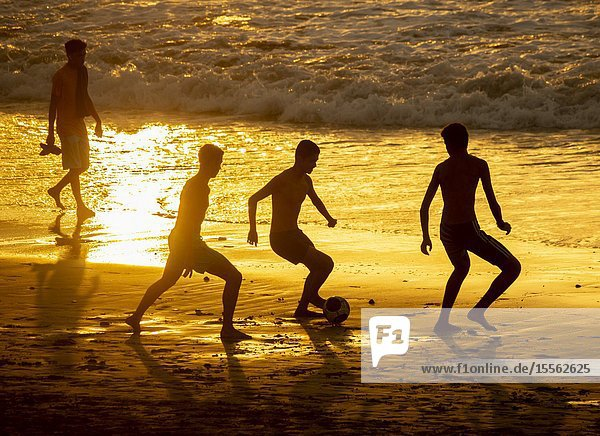 Playa de Las Canteras beach  Las Palmas  Gran Canaria  Canary Islands  Spain. Teenagers playing football at sunset on the city beach in Las Palmas on Gran Canaria.