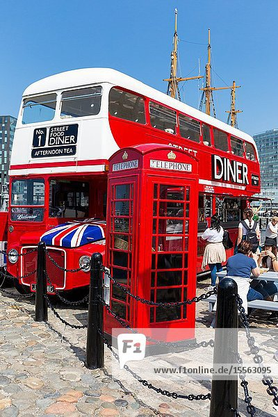 Routemaster bus converted into street cafe diner restaurant facility. Liverpool albert docks. Tourism in Merseyside England UK. Old fashioned Telephone box.