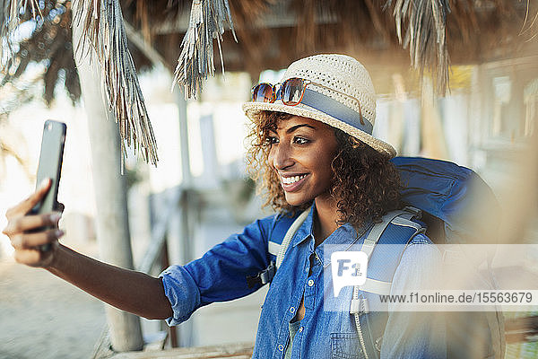 Happy young female backpacker taking selfie with camera phone