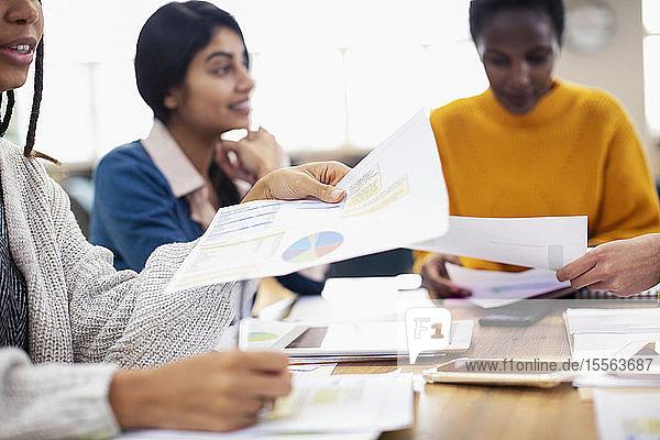 Businesswomen discussing paperwork in meeting