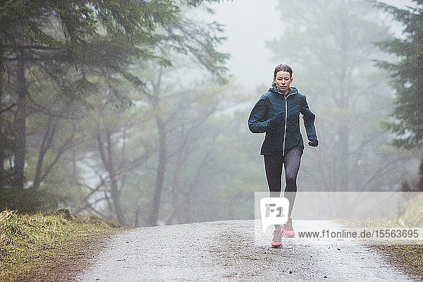 Woman jogging in rainy woods