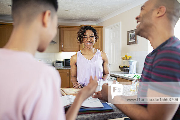 Happy family doing homework and cooking in kitchen