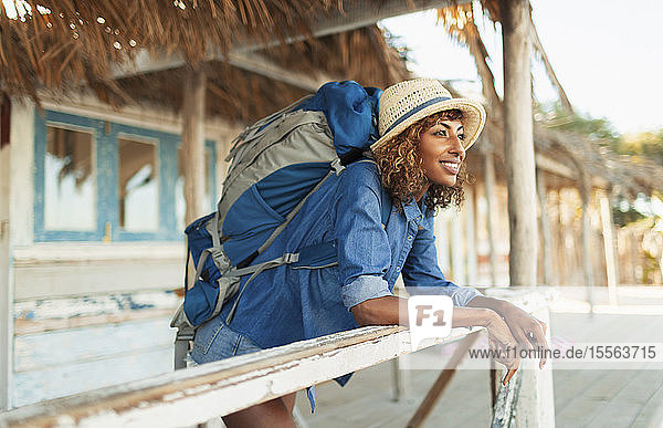 Happy young female backpacker on beach hut patio